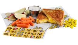 kids meal featuring grilled cheese sandwich, ranch dip, mini candies, carrots, apple slices and stickers