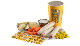 kids meal featuring ham and cheese rollups, small drink, apple slices, carrots, ranch dip, stickers